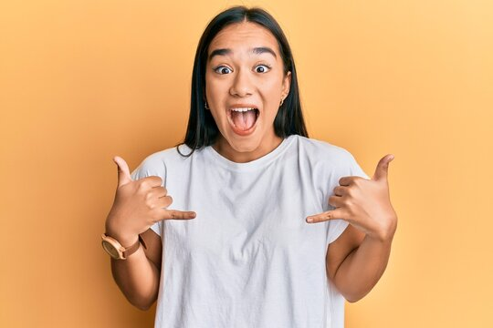 Young asian woman doing shaka sign with hands celebrating crazy and amazed for success with open eyes screaming excited.