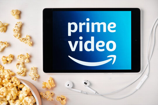 Amazon prime video logo on the screen of the tablet laying on the white table and sprinkled popcorn on it. Apple earphones near the tablet, August 2020, San Francisco, USA