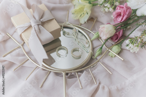Happy Women's and Mother's day. Stylish gift, jewelry and  bouquet on boho mirror on soft fabric