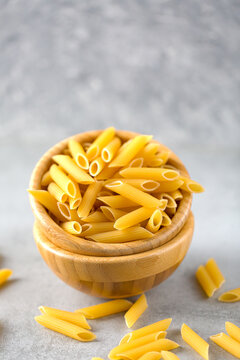 Uncooked yellow pasta in a wooden bowl on gray table. Selective focus. Italian food concept. Vertical orientation