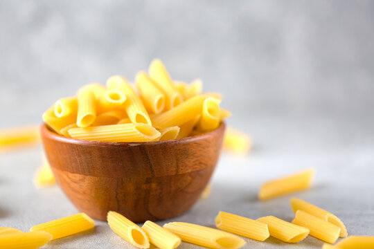 Uncooked yellow pasta in a wooden bowl on gray table. Selective focus. Italian food concept. Copy space,