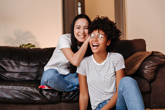 Two young and beautiful girls with smiles on their faces are resting and having fun sitting on a big sofa