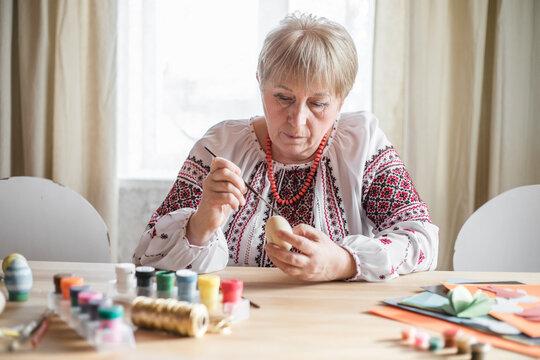 Retired  woman painted easter egg in Ukrainian shirt. DIY craft easter eggs