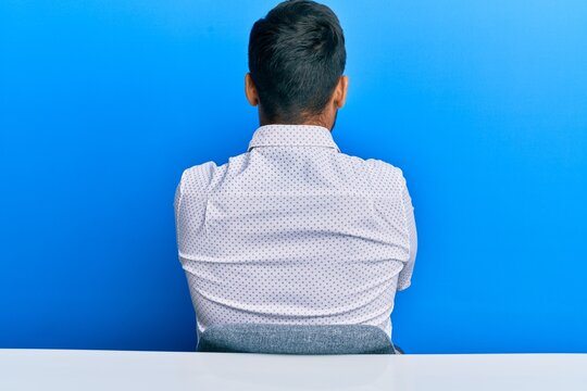 Handsome hispanic man wearing business clothes sitting on the table standing backwards looking away with crossed arms