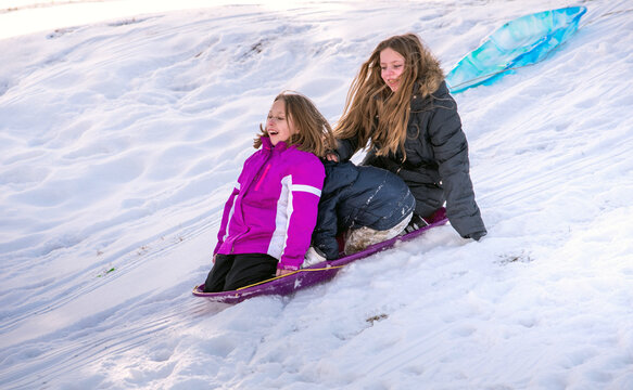 Two Sister Sit With A Little Brother As They Slide Down A Hill On A Purple Plastic Sled