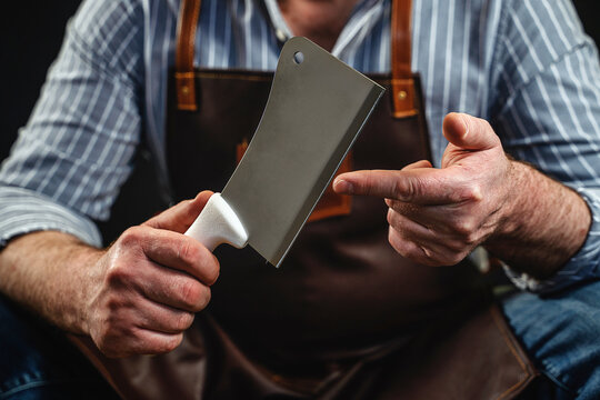 Midsection Of Man Holding Meat Cleaver Against Black Background