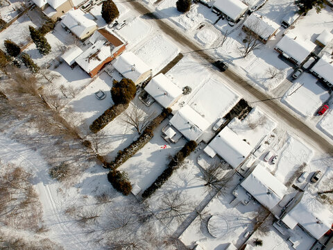 Aerial view of the city. Hundreds of houses bird eye top view suburb urban housing development. Quite neighbourhood covered in snow, Canada. Winter season.