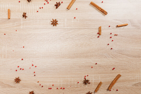 Light wooden background for serving different dishes or inserting inscriptions. Spices, cinnamon, and star anise are scattered in the background