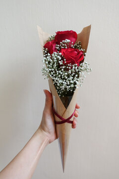 Close-up Of Hand Holding Red Rose Against Wall