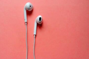 Fototapeta Close-up Of In-ear Headphones Over Coral Background obraz