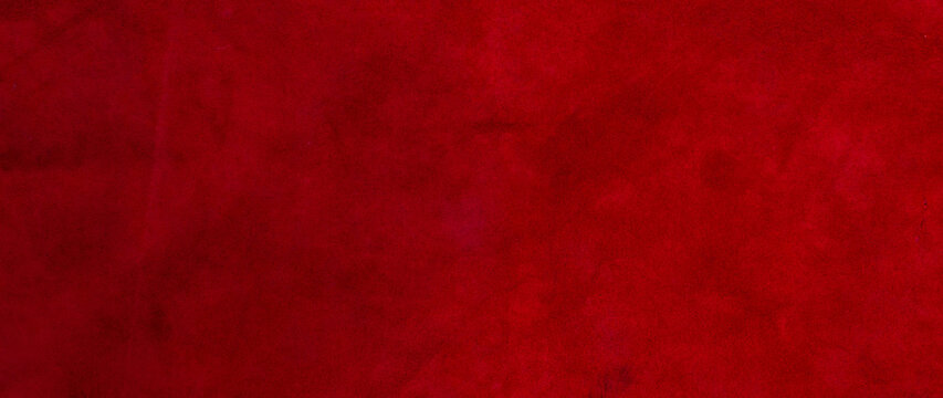 Red matte background of suede fabric, closeup. Velvet texture of seamless leather. Felt