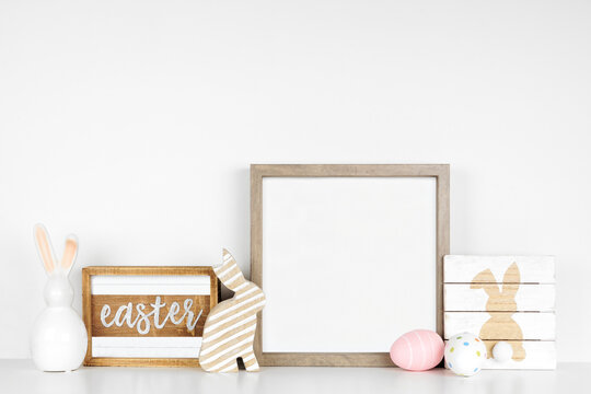 Mock up wood frame with Easter decor on a wood shelf. Shabby chic wood signs, eggs, bunnies. Square frame against a white wall. Copy space.