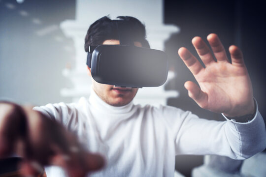 watches videos and works in virtual reality. 3d glasses of black color on the face. 5G data transmission modern digital technology is available. the programmed screen graph is in the air.