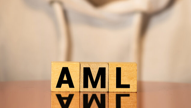 AML anti money laundering acronym on wooden blocks. Government policy and word economy concept.