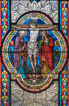 VIENNA, AUSTIRA - OCTOBER 22, 2020: The Crucifixion on the stained glass in  in church Pfarrkirche Kaisermühlen by workroom Tiroler Glasmalerei-Anstalt from end of 19. cent..
