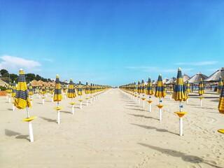 Row Of Umbrellas On Beach Against Blue Sky