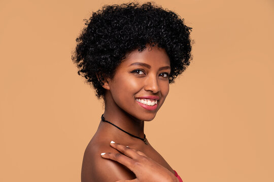 Beauty portrait of african american woman with delicate makeup. Beige studio background. Smiling beautiful afro girl looking at camera.Curly black hair.