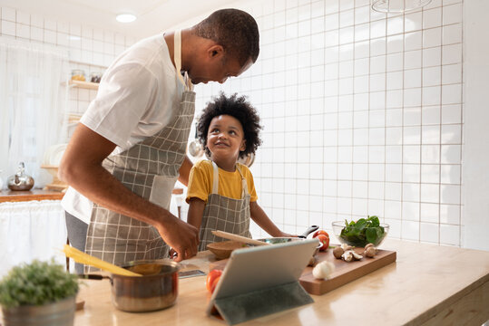 Black African American Father and son doing online cooking with digital tablet in kitchen
