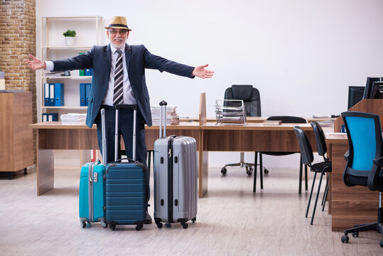 Old male employee preparing for travel in the office