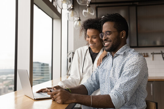 Virtual shoppers. Loving black spouses make purchases online pay for ordered consumer goods in laptop application using credit card. Smiling african married couple check electronic wallet bank account