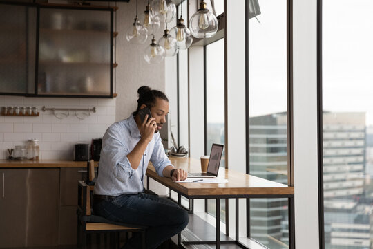 Serious mixed race guy remote employee sit by pc screen call team leader by cell speak about calculation mistake. Hesitating young african man accountant talk to colleague by phone ask to specify data