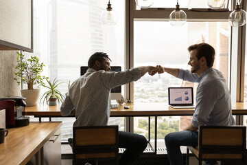Fototapeta Well done, buddy. Motivated diverse young men coworkers bump fists on workplace feel excited achieve common goal. Two workers international business team members share success glad to help one another obraz