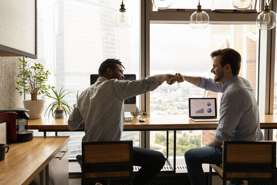 Well done, buddy. Motivated diverse young men coworkers bump fists on workplace feel excited achieve common goal. Two workers international business team members share success glad to help one another