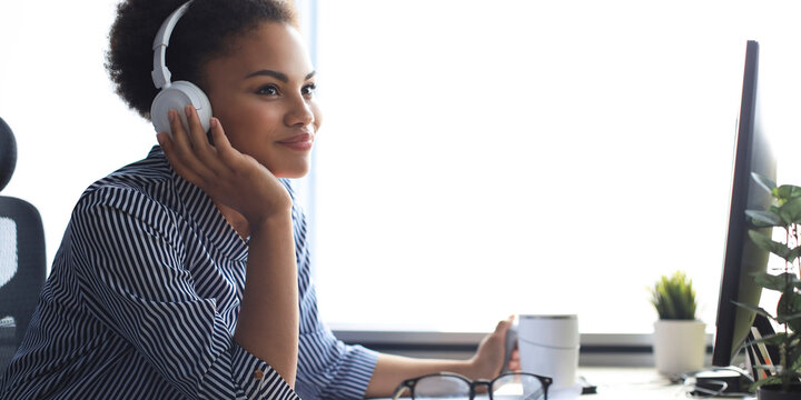 Young african american woman having a break and listening music in headphones sitting on working place.