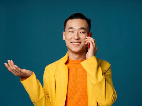 Asian man gesturing with his hands and talking on the phone on a blue background yellow jacket orange sweater