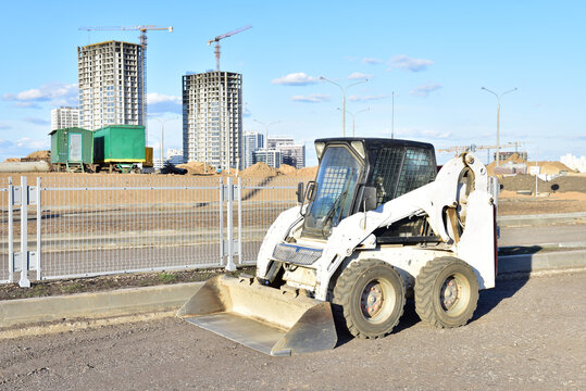 Skid-steer loader for loading and unloading works on city streets. Сompact construction equipment for work in limited conditions. Road repair at construction site. Tower cranes during construction
