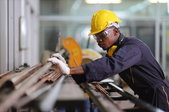 African American mechanic engineer worker is choosing copper tube for sawing while working in coolant factory with copy space