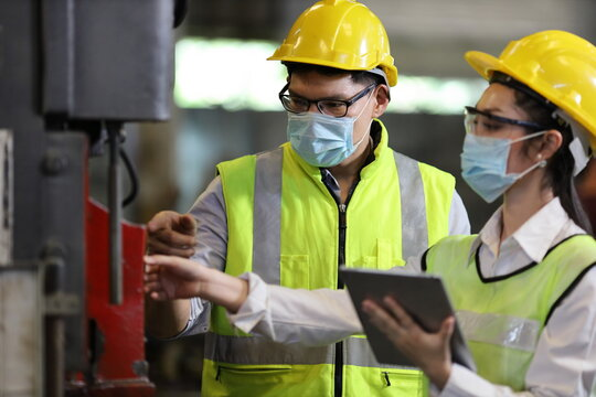 Team of engineer in full safety equipment with facial mask is working and inspecting the heavy industrial factory for new normal during coronavirus or covid-19 pandemic