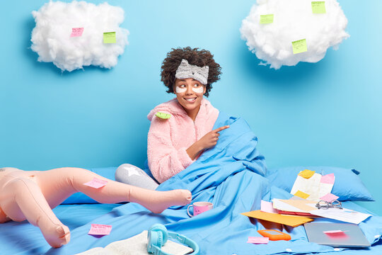 Cheerful African American girl in soft nightwear poses under blanket works from home being on self isolation at home has deadline and paperwork no live communication isolated over blue background