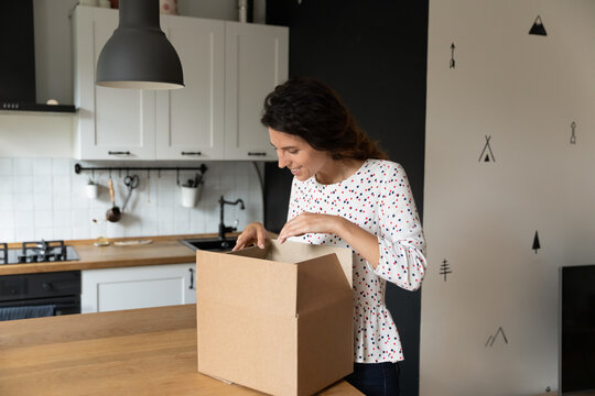 Excited millennial Caucasian woman unpack cardboard box in home kitchen shopping online from home. Happy young female buyer or client unbox package with internet order. Delivery service concept.