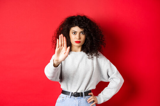 Confident tensed woman extend hand to say stop, disapprove action and prohibit it, make no gesture, standing on red background and forbid something
