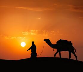 Fototapeta Cameleer (camel driver) with camels in dunes of Thar desert. Raj