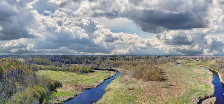 river between spring meadow and forest aerial view