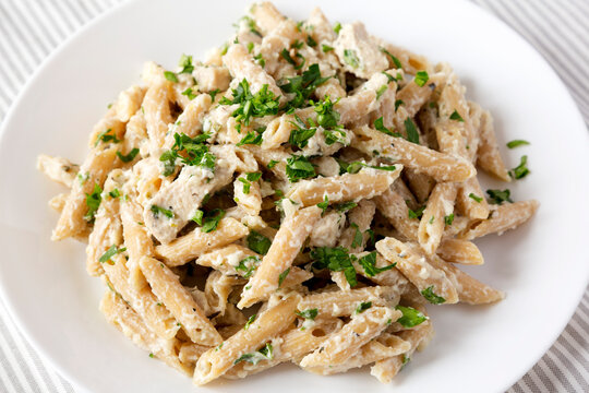 Homemade Chicken Alfredo Penne with Parsley on a white plate, low angle view. Close-up.