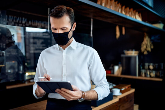 Waiter restaurant owner wearing mask using digital tablet
