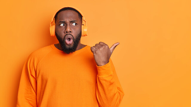 Stupefied dark skinned African American man with thick beard points thumb away on empty space wears casual jumper and stereo headphones listens audio book isolated over vivid orange background.