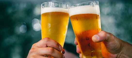 Obraz Close-up view of a two glass of beer in hand. Beer glasses clinking at outdoor bar or pub - fototapety do salonu