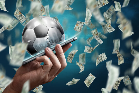 Online sports betting. Dollars are falling on the background of a hand with a smartphone and a soccer ball. Creative background, gambling.