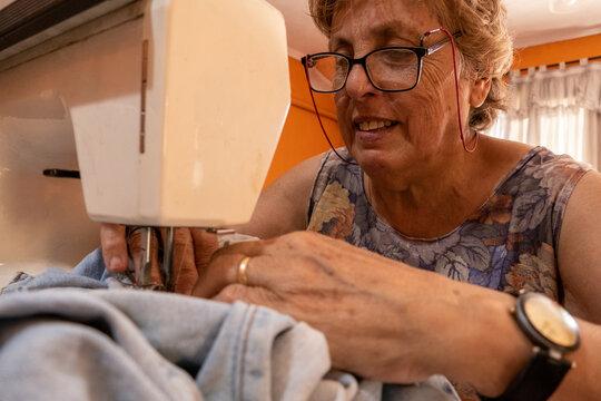 La abuela cosiendo con maquina de cocer la ropa de sus nietos