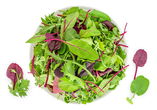 Salad leaves in a bowl isolated on white background. Mix fresh leaves of arugula, lettuce and  spinach leaf. Top view