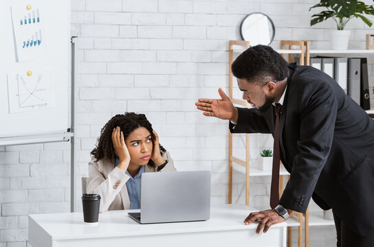 Displeased male boss scolding upset female employee for mistake in company project or missed deadline at office