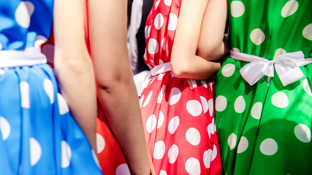 Group of female in cocktail spotted dresses