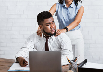 Obraz Lady boss sexually molesting her attractive male subordinate, putting hands on his shoulders at company office - fototapety do salonu