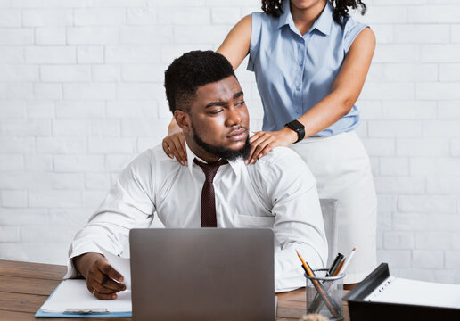 Lady boss sexually molesting her attractive male subordinate, putting hands on his shoulders at company office