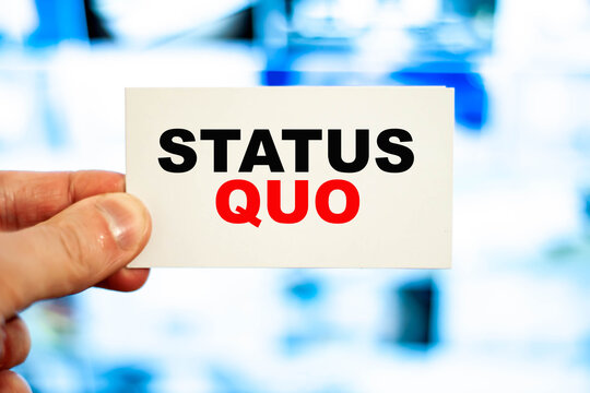 Concept of a person holding a business card with the words - Status quo