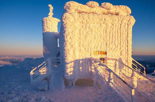 peak of Sniezka mountain in Karkonosze in Poland and Czech republic border during winter sunset